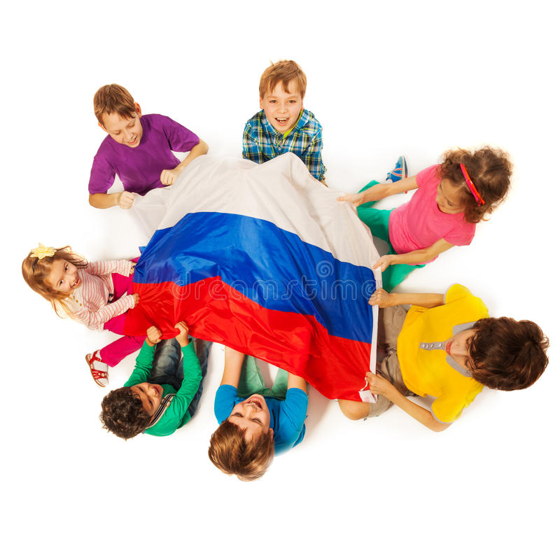 Kids around the flag of Russian Federation. Top view of seven happy kids sitting around and holding the Russian Federation flag, isolated on white background stock photography
