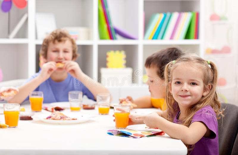 Kids around the table eating stock images