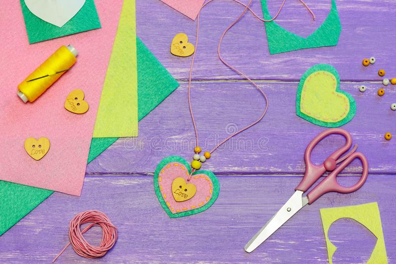 Simple felt heart pendant necklace. Valentines day pendant necklace made of felt, beads and wooden button with text love. Kids art workplace. Gift for mum. Fun stock images