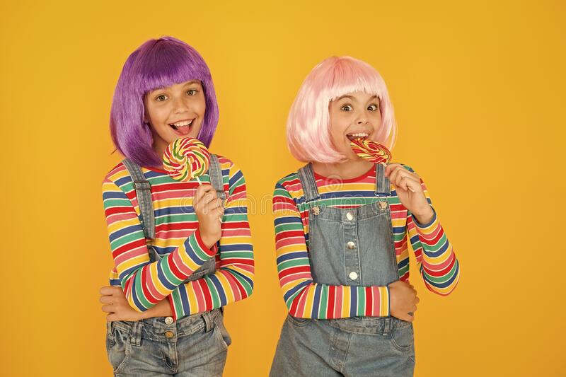 Kids with artificial hairstyles eating lollipops. Anime convention. Vibrant characters fantastical themes. Modern. Childhood. Childrens day. Anime cosplay party stock photo