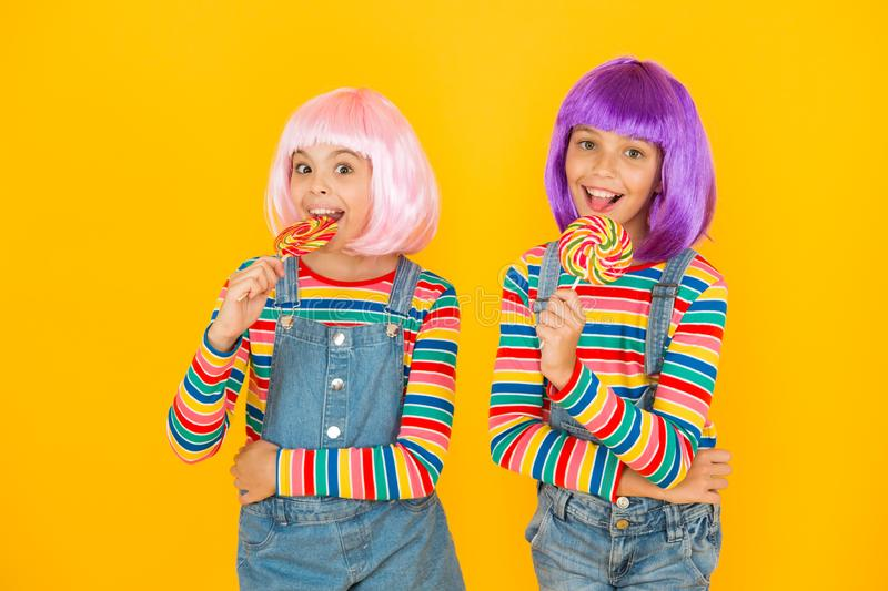 Kids with artificial hairstyles eating lollipops. Anime convention. Vibrant characters fantastical themes. Modern royalty free stock photo