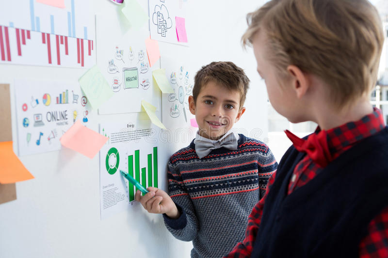 Kids as business executives discussing over whiteboard. In office royalty free stock photos