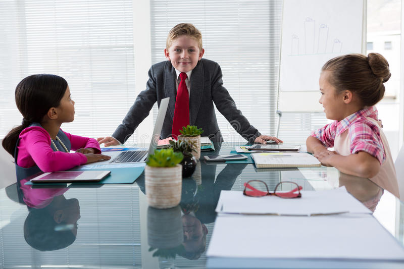Kids as business executives interacting while meeting royalty free stock image