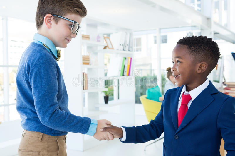 Kids as business executives shaking hands. In office stock photo
