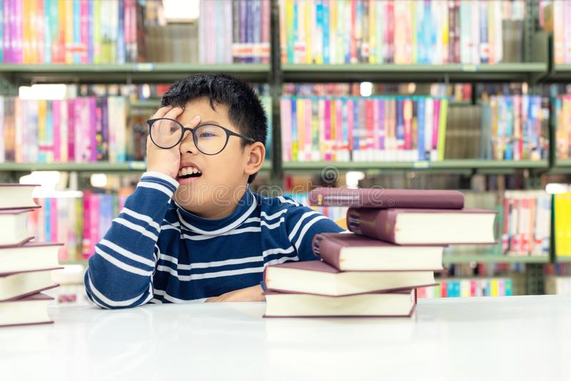 Kids asia boy reading books for education and go to school in library. Education and Lifestyle Concept royalty free stock photo