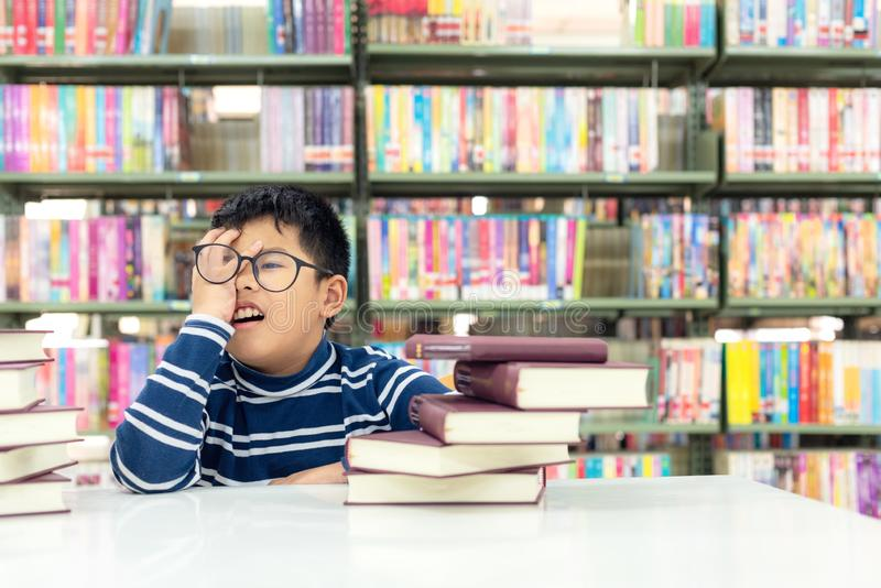 Kids asia boy reading books for education and go to school in library . Education and Lifestyle Concept royalty free stock photo