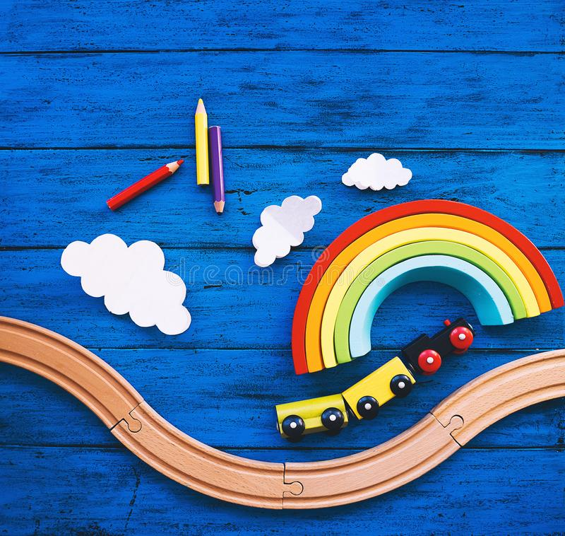 Kids background with toys. Wooden toy train, railway for preschool child, wood rainbow, colored pencils on blue table. Daycare, kindergarten or montessori school royalty free stock photography