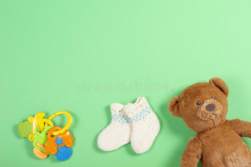 Kids background. White woolen baby socks and teddy bear and toy on green background stock photos