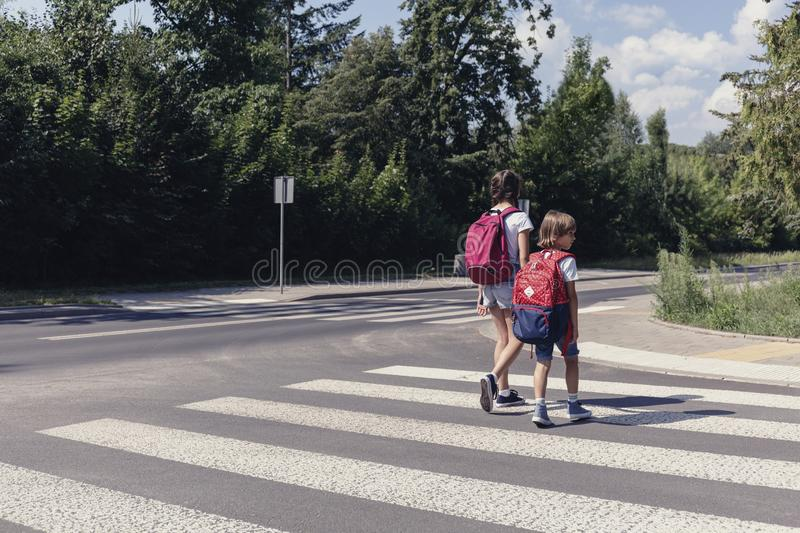Kids with backpacks walking through pedestrian crossing stock photos