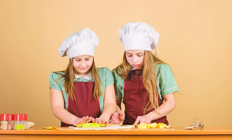 Kids baking cookies together. Kids aprons and chef hats cooking. Homemade cookies best. Family recipe. Cooking skill. Culinary education. Baking ginger cookies royalty free stock image