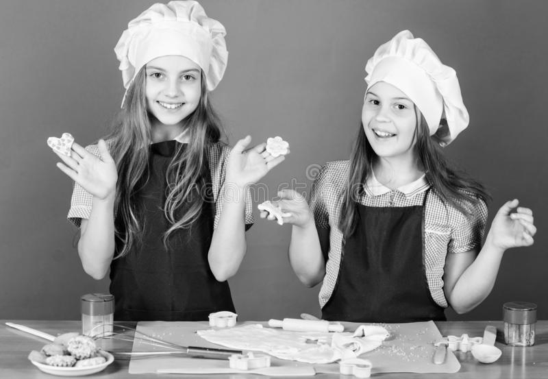 Kids baking cookies together. Kids aprons and chef hats cooking. Family recipe. Culinary education. Mothers day. Baking royalty free stock photo