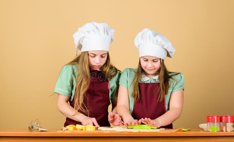 Kids baking cookies together. Kids aprons and chef hats cooking. Homemade cookies best. Family recipe. Cooking skill stock photos