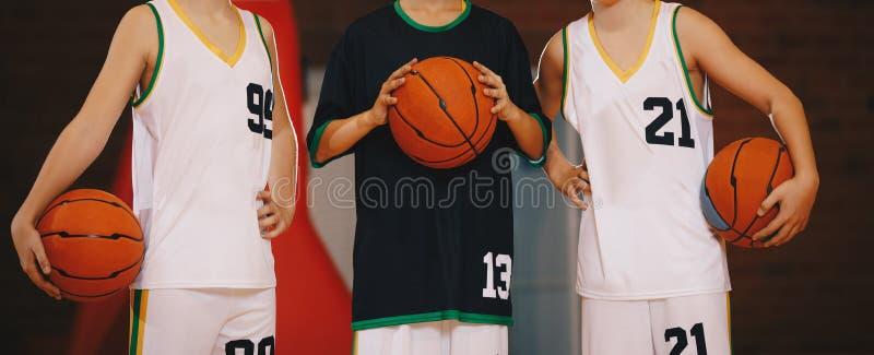 Kids Basketball Team. Young Basketball Players Holding Balls on Basketball Court stock photo