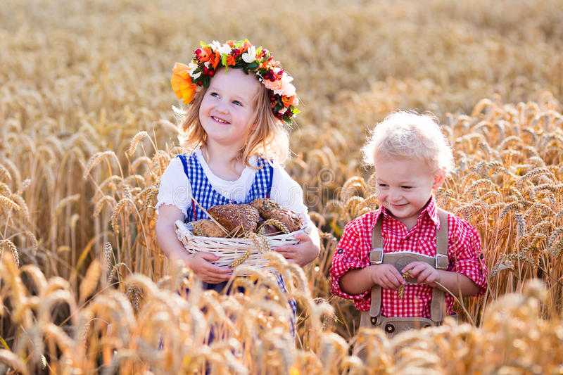 Kids in Bavarian costumes in wheat field stock images