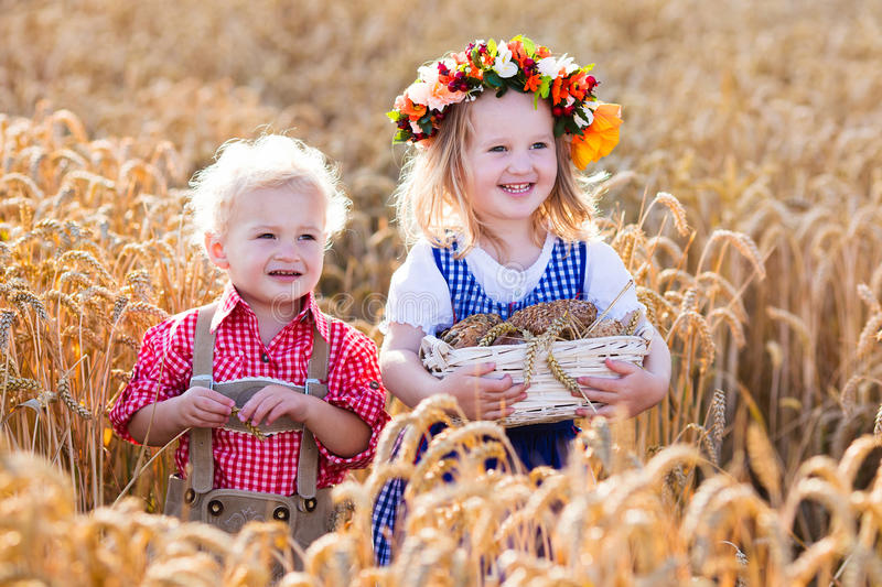 Kids in Bavarian costumes in wheat field stock photos