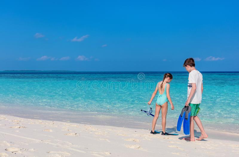 Kids at beach. Little kids with snorkeling equipment on tropical beach having fun during summer vacation royalty free stock photos