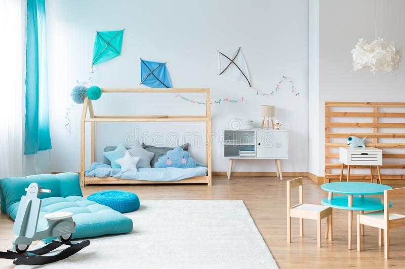 Kids bedroom with handmade furniture. Modern rocking toy and blue mattress on white carpet in kids bedroom with handmade furniture stock images