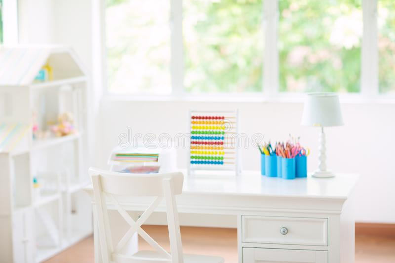 Kids bedroom with wooden desk and doll house stock images