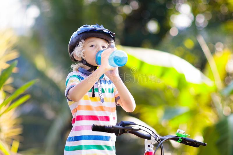 Kids on bike. Child on bicycle. Kid cycling. Kids on bike in park. Children going to school wearing safe bicycle helmets. Little boy biking on sunny summer day stock photography