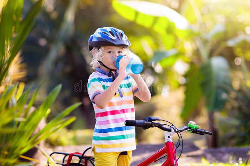 Kids on bike. Child on bicycle. Kid cycling. Kids on bike in park. Children going to school wearing safe bicycle helmets. Little boy biking on sunny summer day stock images