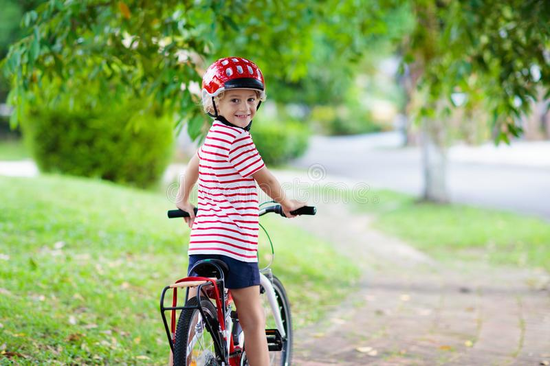 Kids on bike. Child on bicycle. Kid cycling. Kids on bike in park. Children going to school wearing safe bicycle helmets. Little boy biking on sunny summer day royalty free stock photo