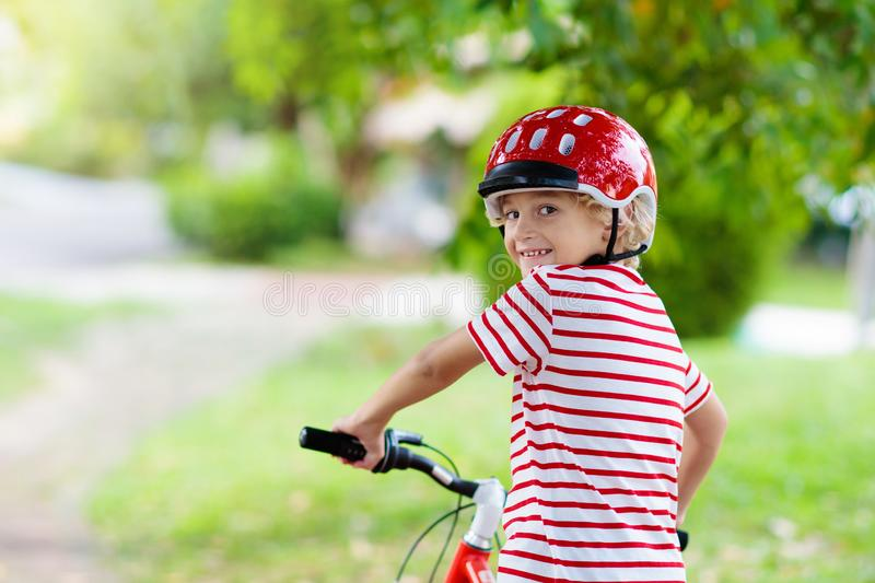 Kids on bike. Child on bicycle. Kid cycling. Kids on bike in park. Children going to school wearing safe bicycle helmets. Little boy biking on sunny summer day royalty free stock photos