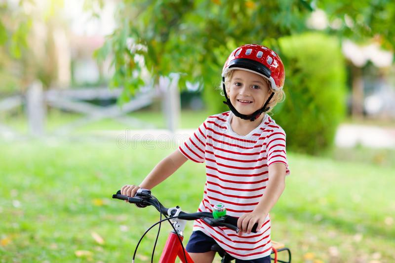 Kids on bike. Child on bicycle. Kid cycling. Kids on bike in park. Children going to school wearing safe bicycle helmets. Little boy biking on sunny summer day stock image