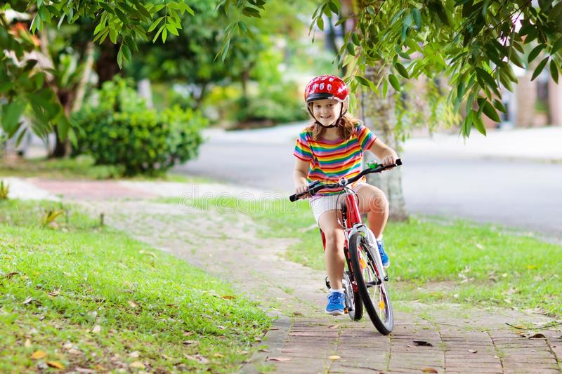 Kids on bike. Child on bicycle. Kid cycling. Kids on bike in park. Children going to school wearing safe bicycle helmets. Little girl biking on sunny summer day royalty free stock photo