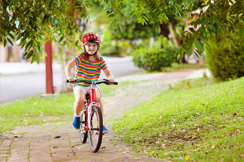 Kids on bike. Child on bicycle. Kid cycling. Kids on bike in park. Children going to school wearing safe bicycle helmets. Little girl biking on sunny summer day royalty free stock photography