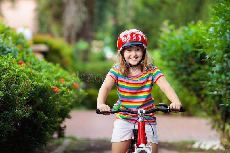 Kids on bike. Child on bicycle. Kid cycling. Kids on bike in park. Children going to school wearing safe bicycle helmets. Little girl biking on sunny summer day royalty free stock image