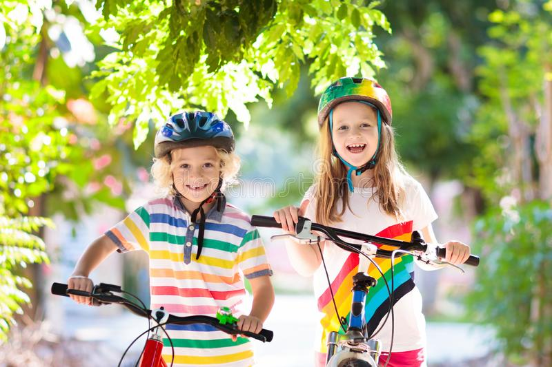 Kids on bike. Children on bicycle. Child biking. Kids on bike in park. Children going to school wearing safe bicycle helmets. Little boy and girl biking on sunny royalty free stock images