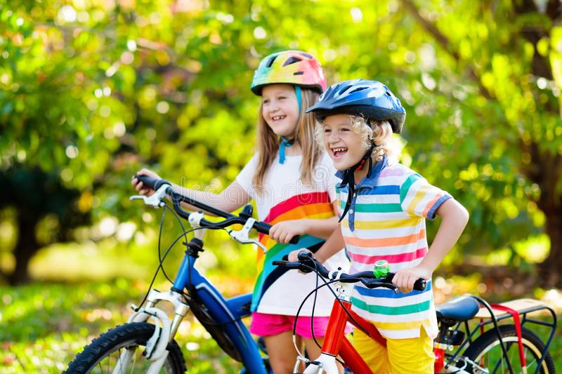 Kids on bike. Children on bicycle. Child biking. Kids on bike in park. Children going to school wearing safe bicycle helmets. Little boy and girl biking on sunny royalty free stock photography