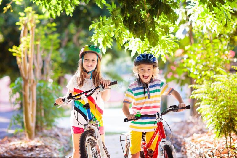 Kids on bike. Children on bicycle. Child biking. Kids on bike in park. Children going to school wearing safe bicycle helmets. Little boy and girl biking on sunny royalty free stock photo