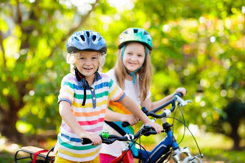 Kids on bike. Children on bicycle. Child biking. Kids on bike in park. Children going to school wearing safe bicycle helmets. Little boy and girl biking on sunny stock images
