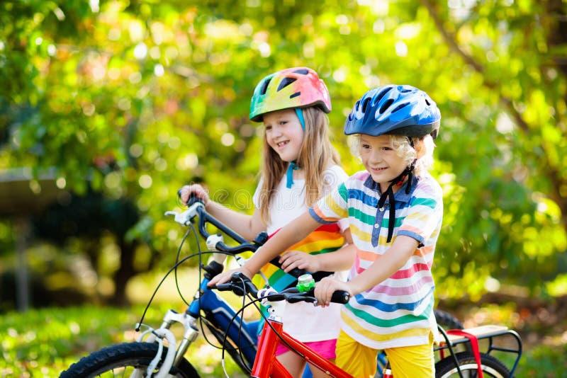 Kids on bike. Children on bicycle. Child biking. Kids on bike in park. Children going to school wearing safe bicycle helmets. Little boy and girl biking on sunny royalty free stock image
