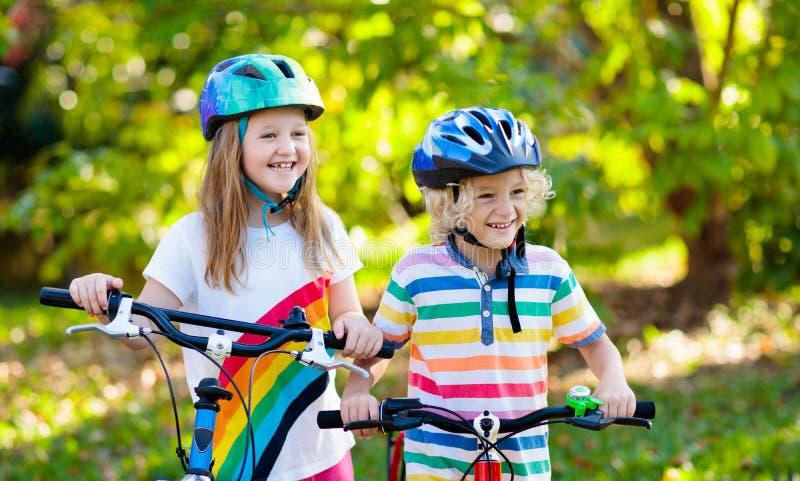 Kids on bike. Children on bicycle. Child biking. Kids on bike in park. Children going to school wearing safe bicycle helmets. Little boy and girl biking on sunny stock photos