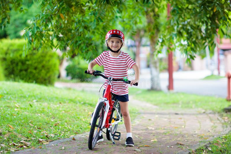 Kids on bike. Child on bicycle. Kid cycling. Kids on bike in park. Children going to school wearing safe bicycle helmets. Little boy biking on sunny summer day stock photos