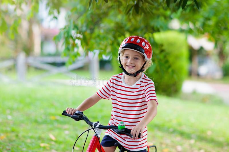 Kids on bike. Child on bicycle. Kid cycling. Kids on bike in park. Children going to school wearing safe bicycle helmets. Little boy biking on sunny summer day stock photo