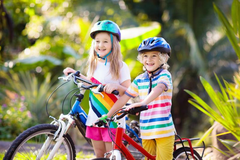 Kids on bike. Children on bicycle. Child biking. Kids on bike in park. Children going to school wearing safe bicycle helmets. Little boy and girl biking on sunny royalty free stock photos