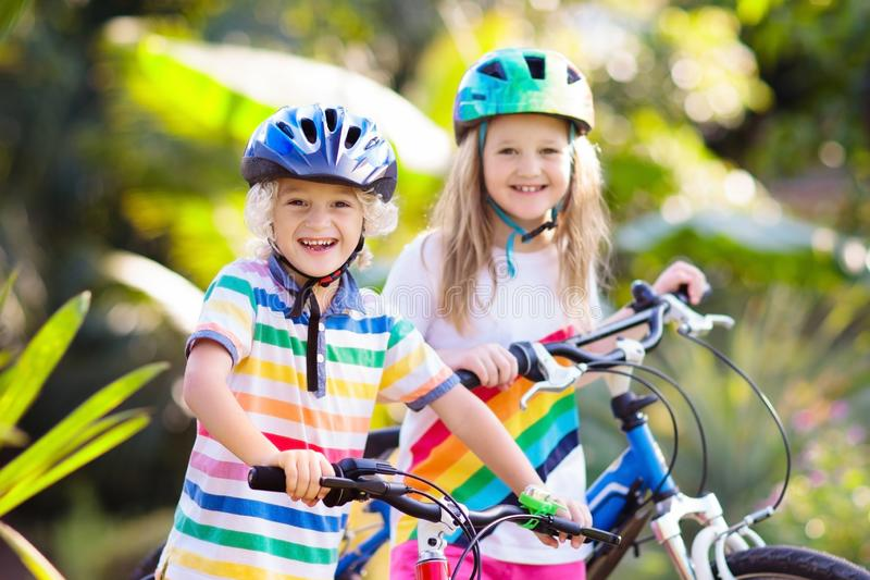 Kids on bike. Children on bicycle. Child biking. Kids on bike in park. Children going to school wearing safe bicycle helmets. Little boy and girl biking on sunny stock image