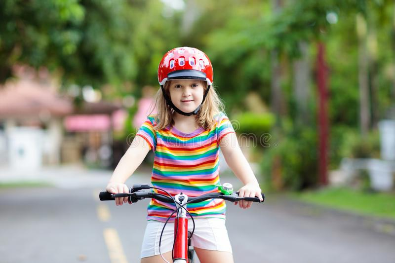 Kids on bike. Child on bicycle. Kid cycling. Kids on bike in park. Children going to school wearing safe bicycle helmets. Little girl biking on sunny summer day stock images