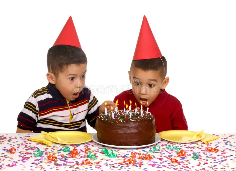 Kids and birthday. Two brothers aged 5 and 6 years ready to enjoy a birthday cake, isolated on white background royalty free stock image