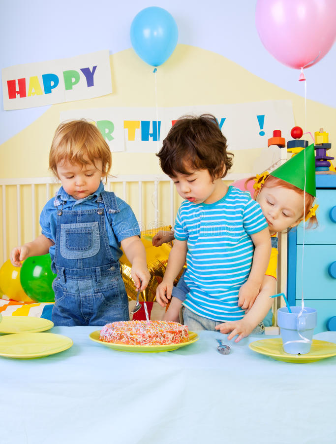 Kids and birthday cake. Kids around birthday cake on birthday party - two boys and girl royalty free stock photos