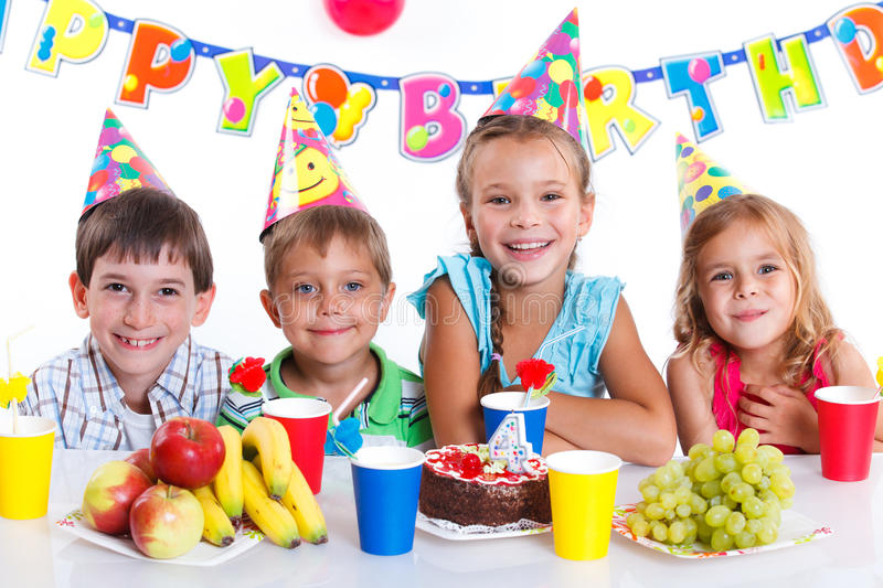 Kids with birthday cake. Group of adorable kids having fun at birthday party with birthday cake royalty free stock images