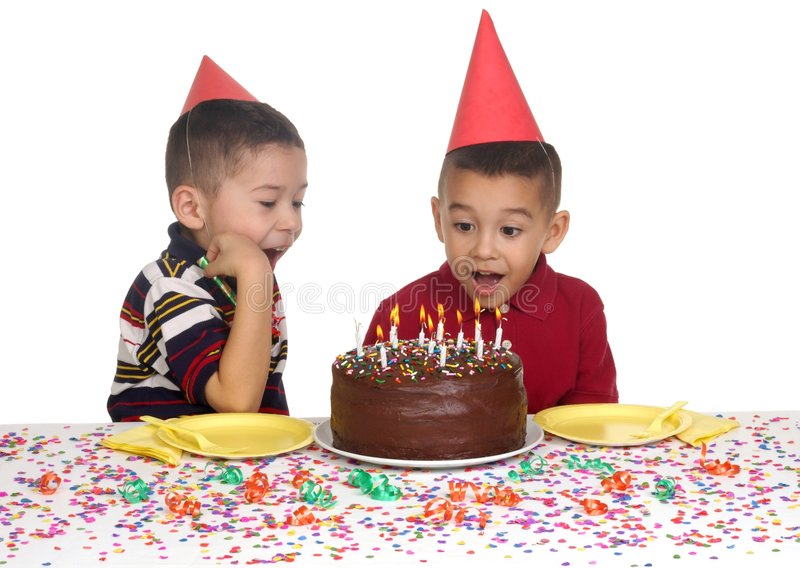 Kids at Birthday Party. Two brothers aged 5 and 6 years, wearing funny party hats and ready to enjoy a birthday cake, isolated on white background stock images