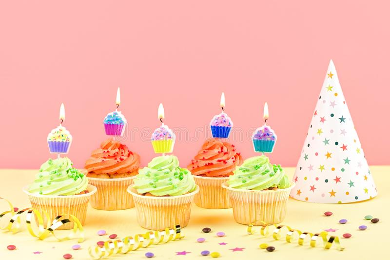 Kids birthday party accessories - colorful cupcakes with burning candles, party hat, streamers, confetti. Copy space. Birthday party accessories and event royalty free stock photo
