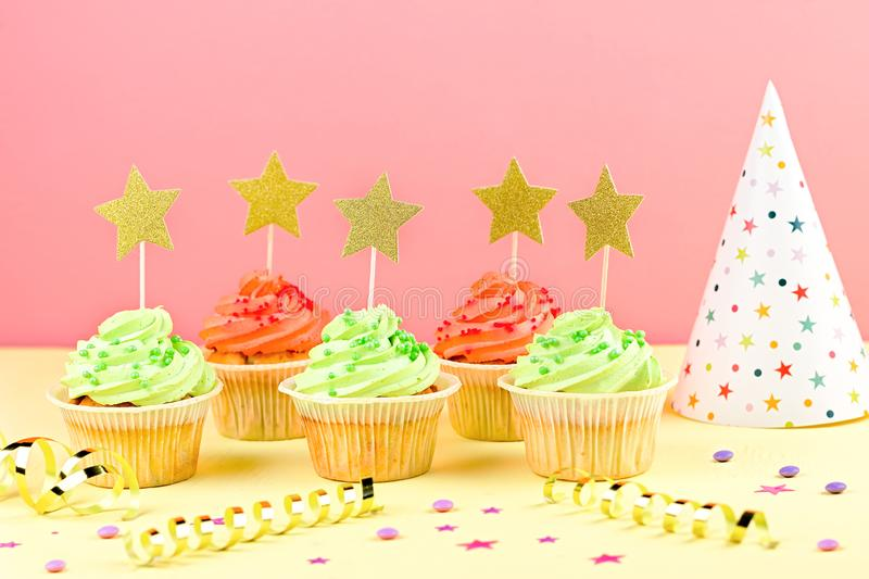 Kids birthday party accessories - colorful cupcakes, party hat, streamers, confetti. Copy space. Birthday party accessories and event supplies background with royalty free stock image