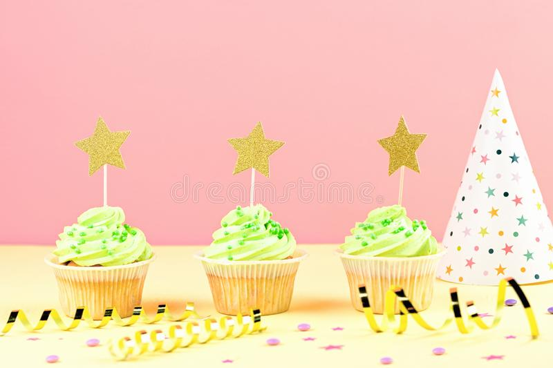 Kids birthday party accessories - colorful cupcakes, party hat, streamers, confetti. Copy space. Birthday party accessories and event supplies background with stock photo
