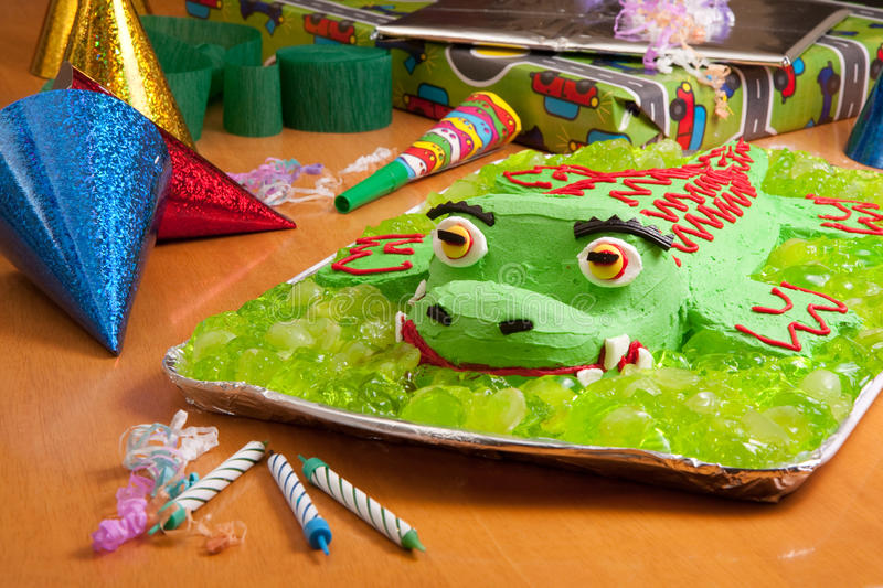 Kids birthday party cake. Crocodile kids birthday cake at kids party surrounded by presents and party hats stock image