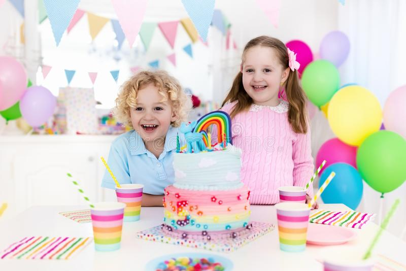 Kids birthday party with cake. Kids birthday party with colorful pastel decoration and rainbow cake. Girl and boy with sweets, candy and fruit. Balloons and royalty free stock images